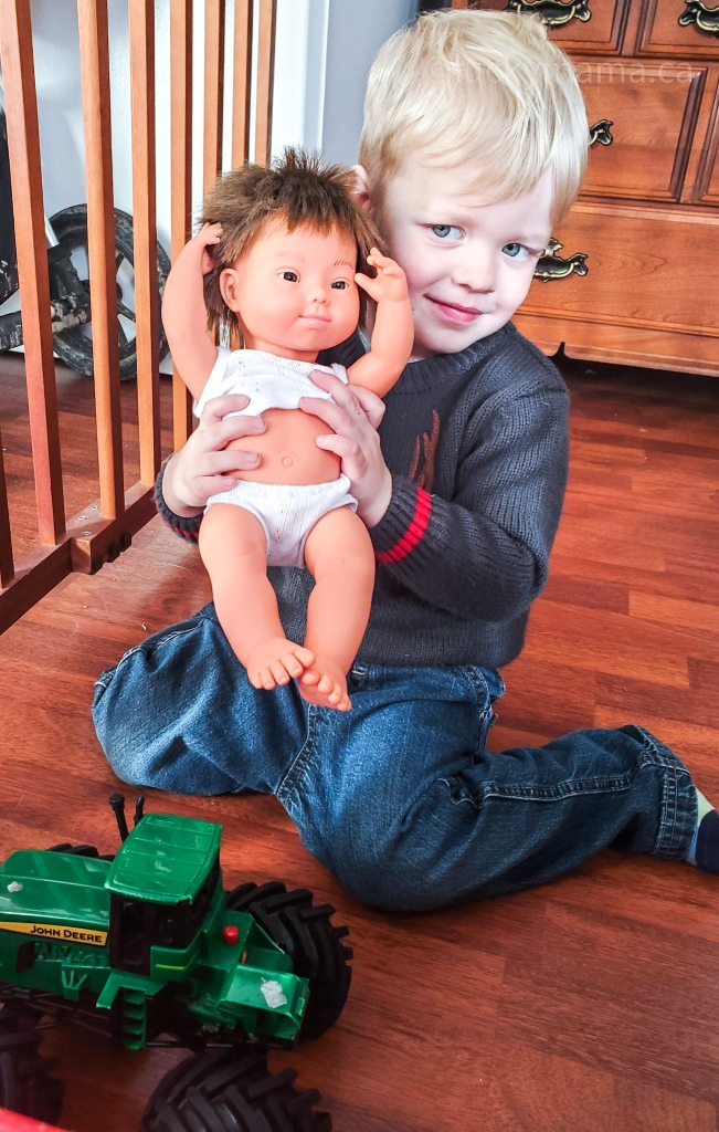 Pictured is Sullivan, the author's blonde haired, grey eyed, 3 year old boy, wearing a sweater and jeans. He holds a toy miniland doll that has realistic features of a child with down syndrome. In front of him is a toy John Deere tractor.